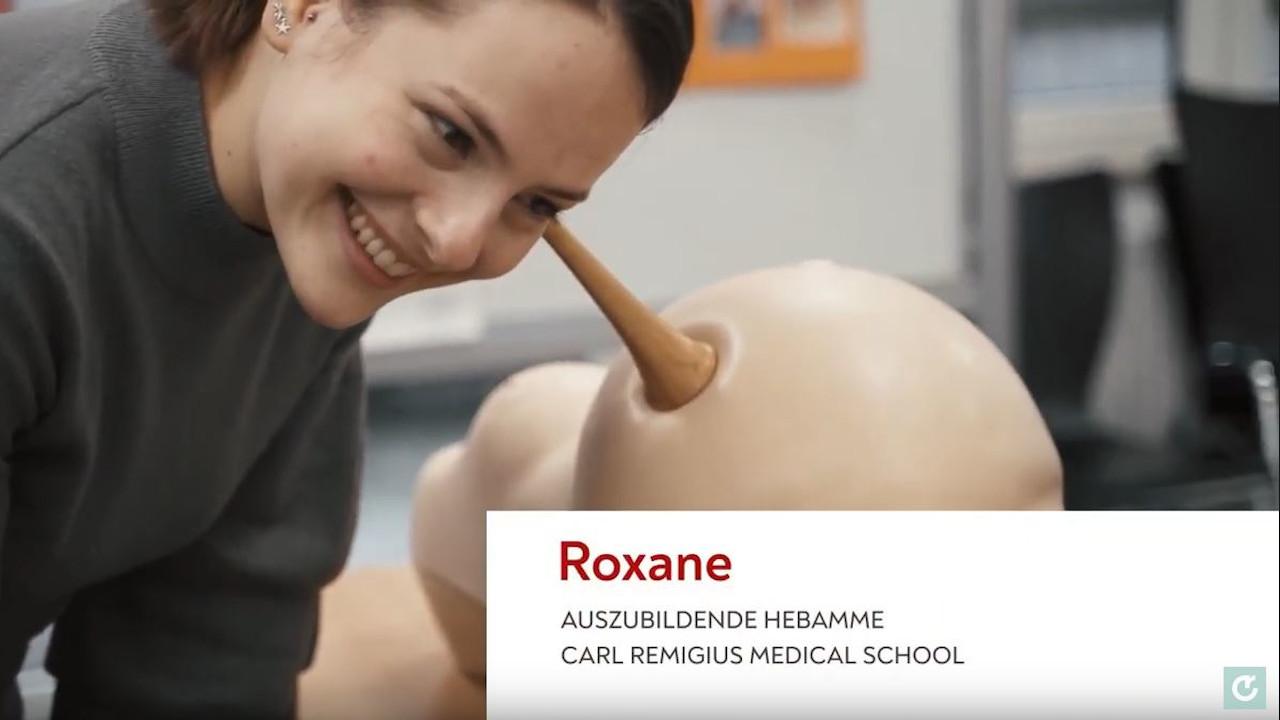 Roxanne, Auszubildende Hebamme, mit einem Hörrohr