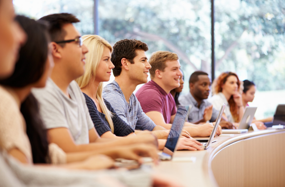 Studierende sitzen in einer Reihe im Hörsaal