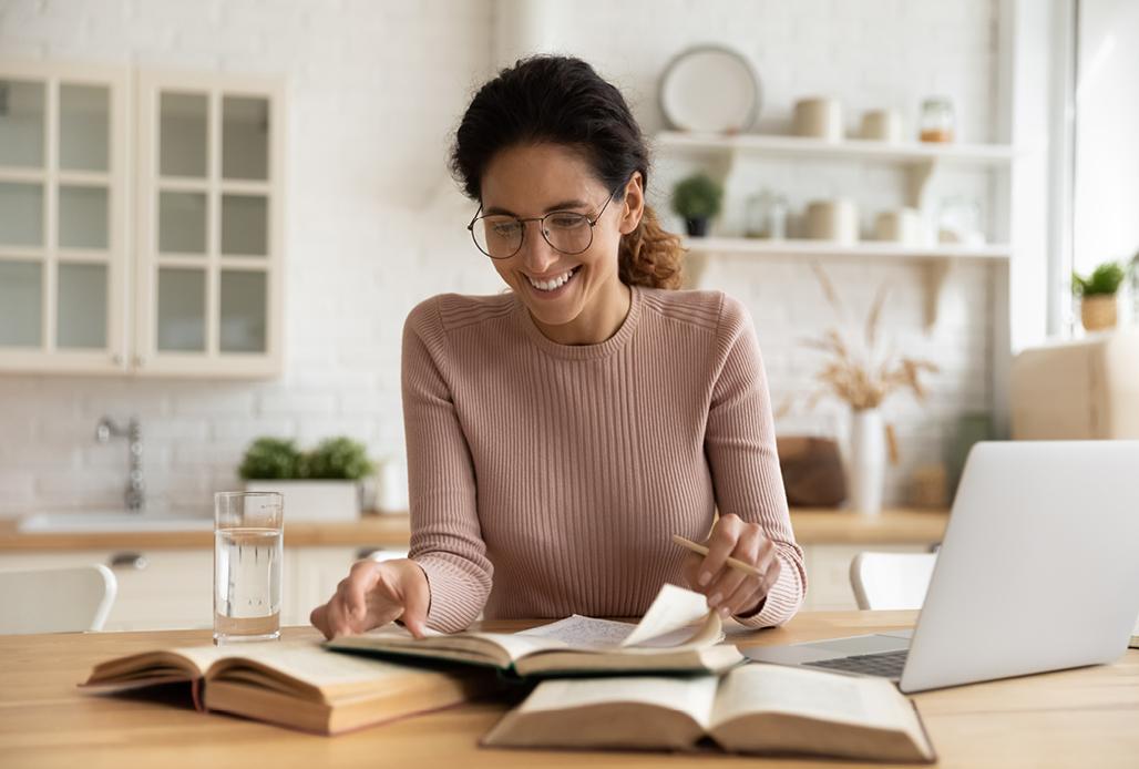 Frau sitzt mit Laptop am Tisch und blättert durch Bücher