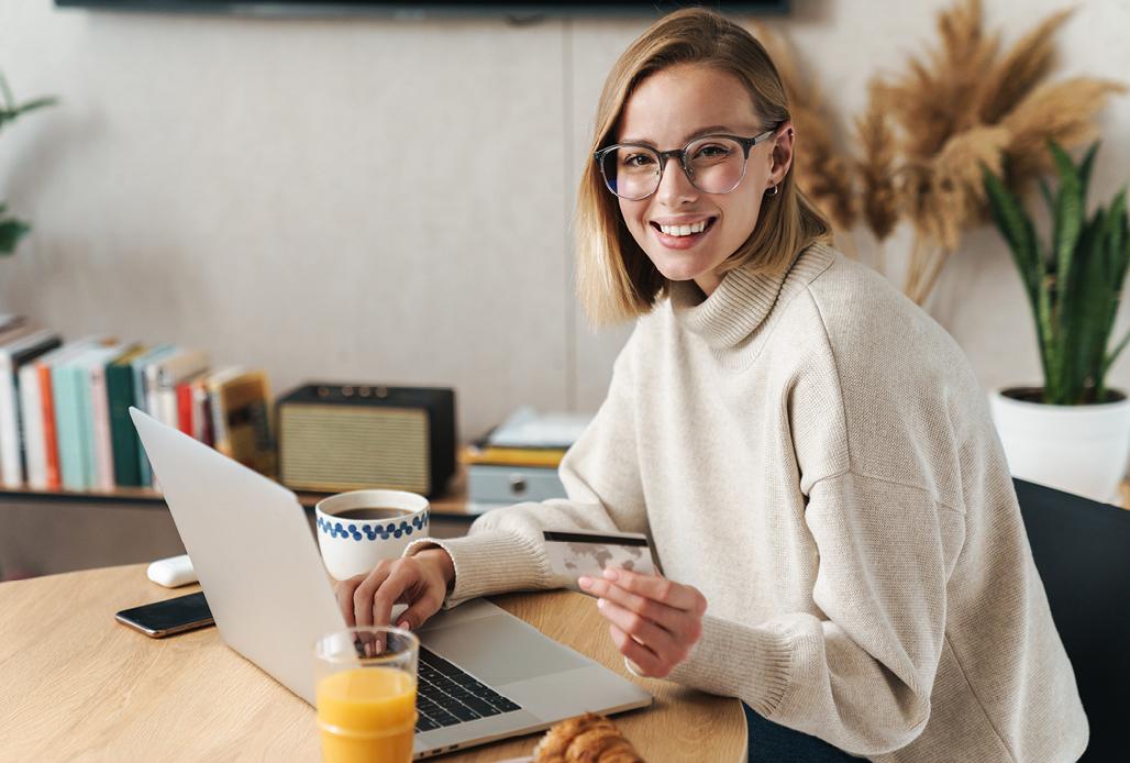 Frau sitzt mit Laptop am Küchentisch