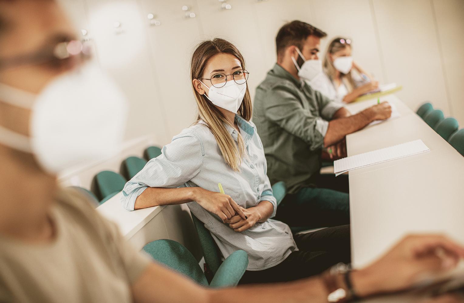 Mehrere Menschen sitzen im Hörsaal und tragen Masken
