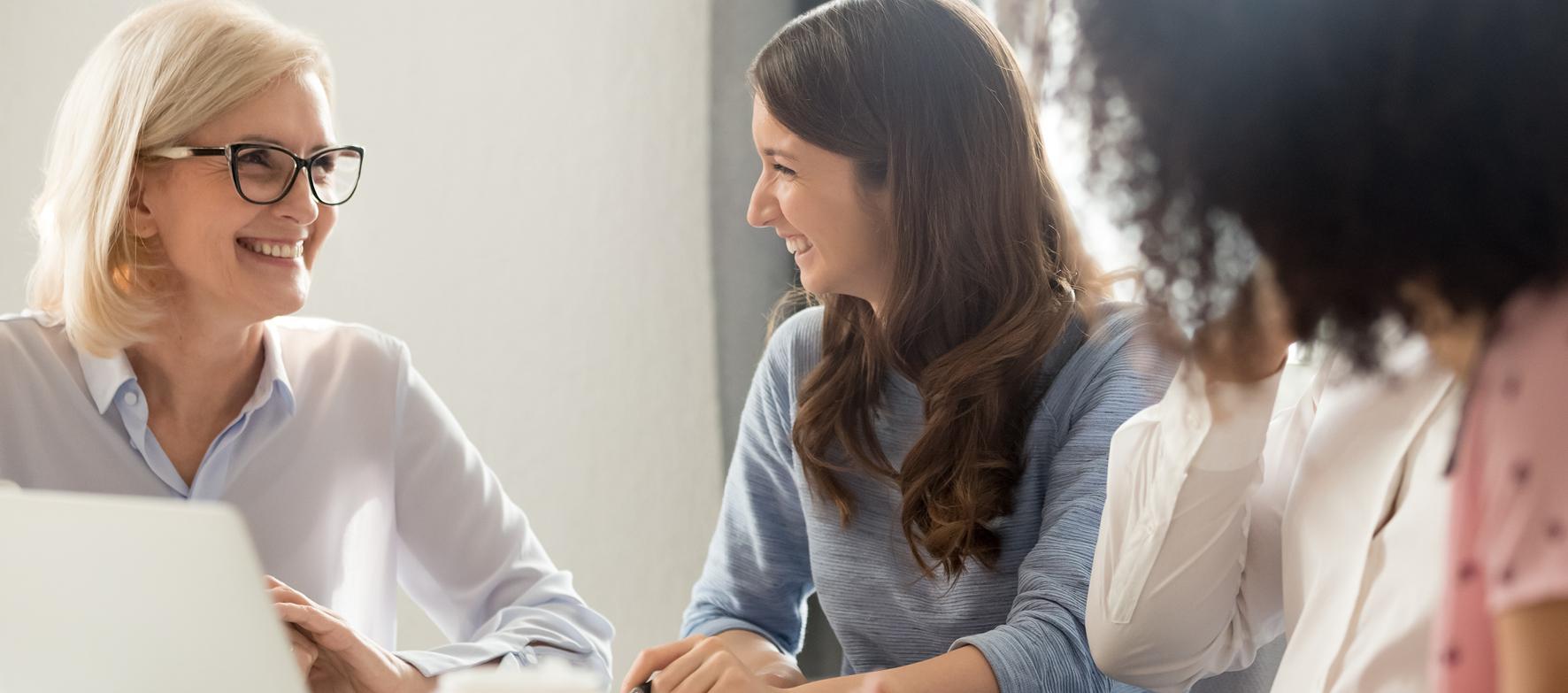 Zwei lachende Frauen am Laptop