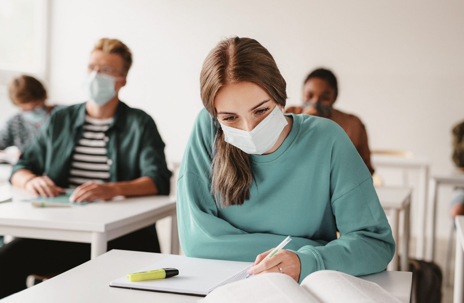 Junge Frau in einem Seminarraum mit Maske schaut in ein Buch