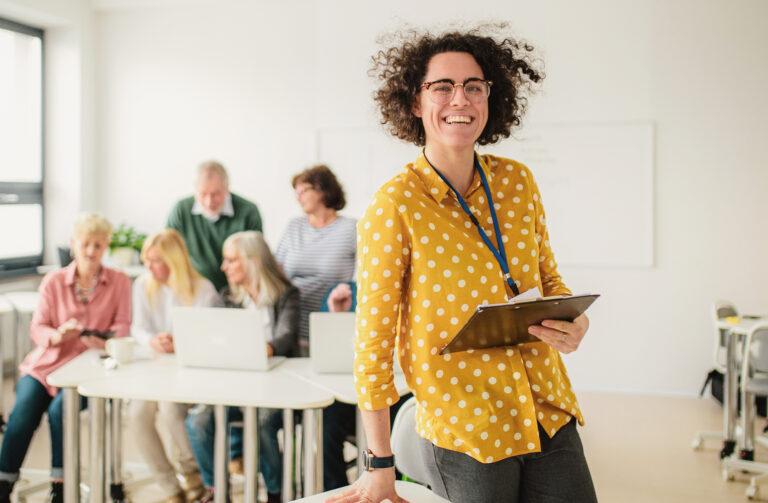 Frau mit Klemmblett steht vor einer Gruppe Menschen im Seminarraum