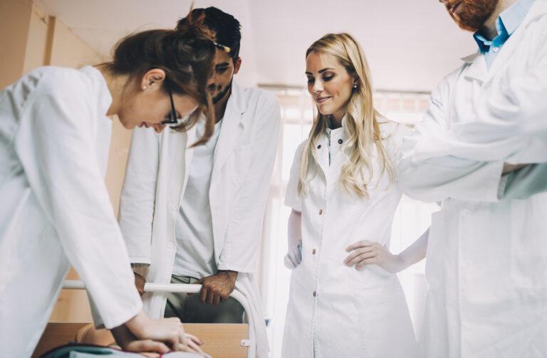 Mehrere junge Ärzte schauen einer anderen bei einer Übung zu