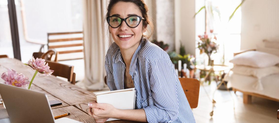 Junge Frau sitzt mit Notizen an einem Tisch vor einem Laptop