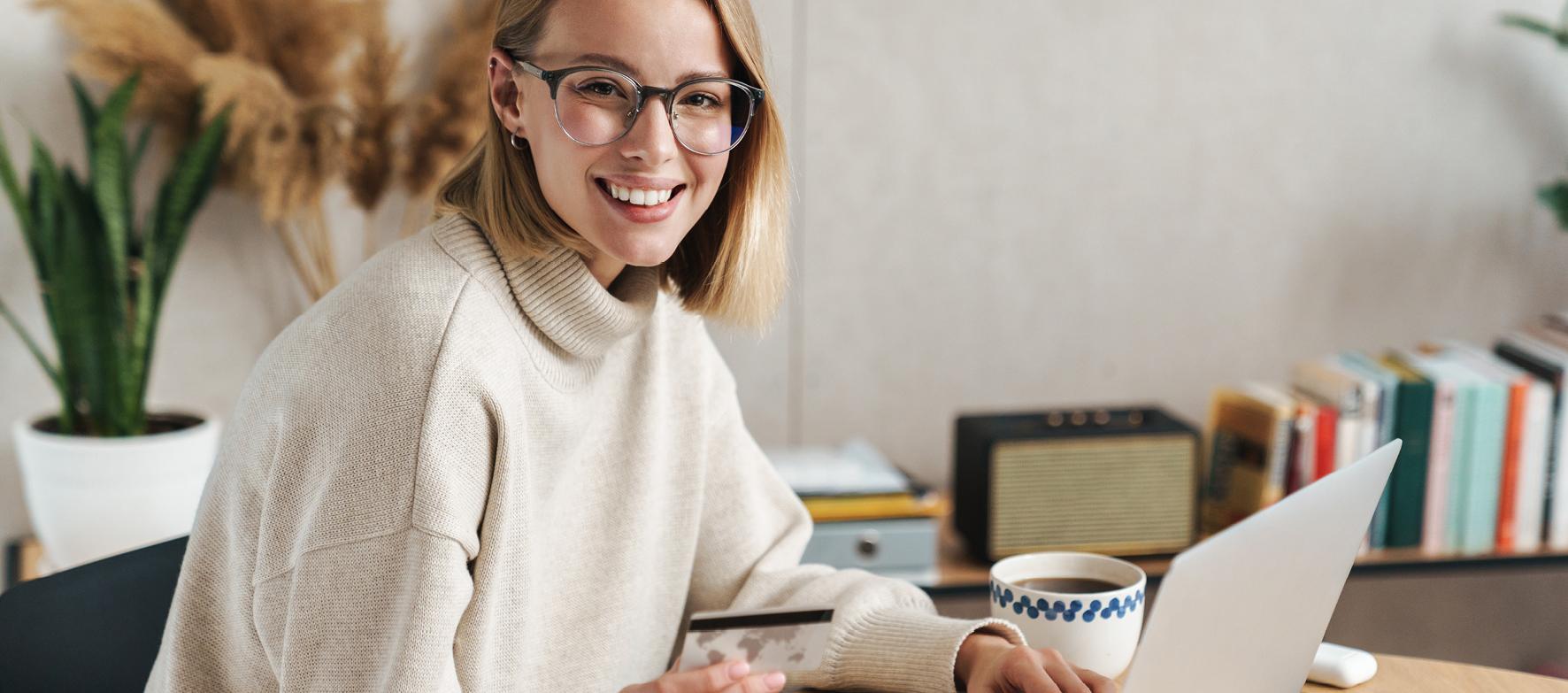 Junge Frau sitzt mit Laptop am Frühstückstisch