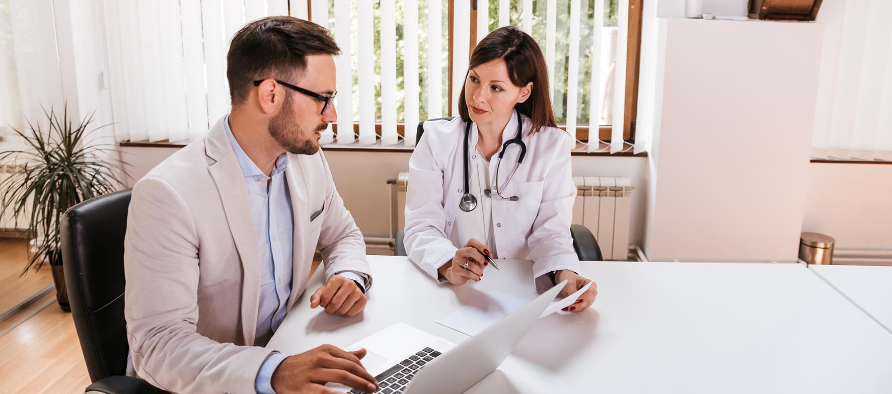 Ärztin und Berater sitzen an einem Tisch mit Papier und Laptop