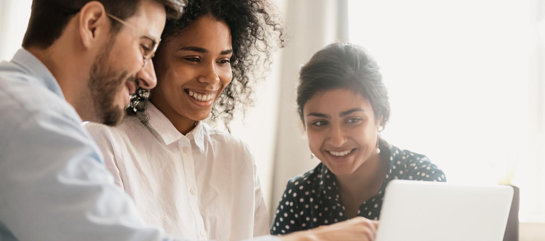 Drei junge Menschen schauen gemeinsam auf einen Laptopbildschirm