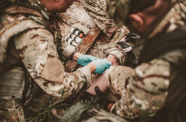 Zwei Soldaten verbinden einen dritten