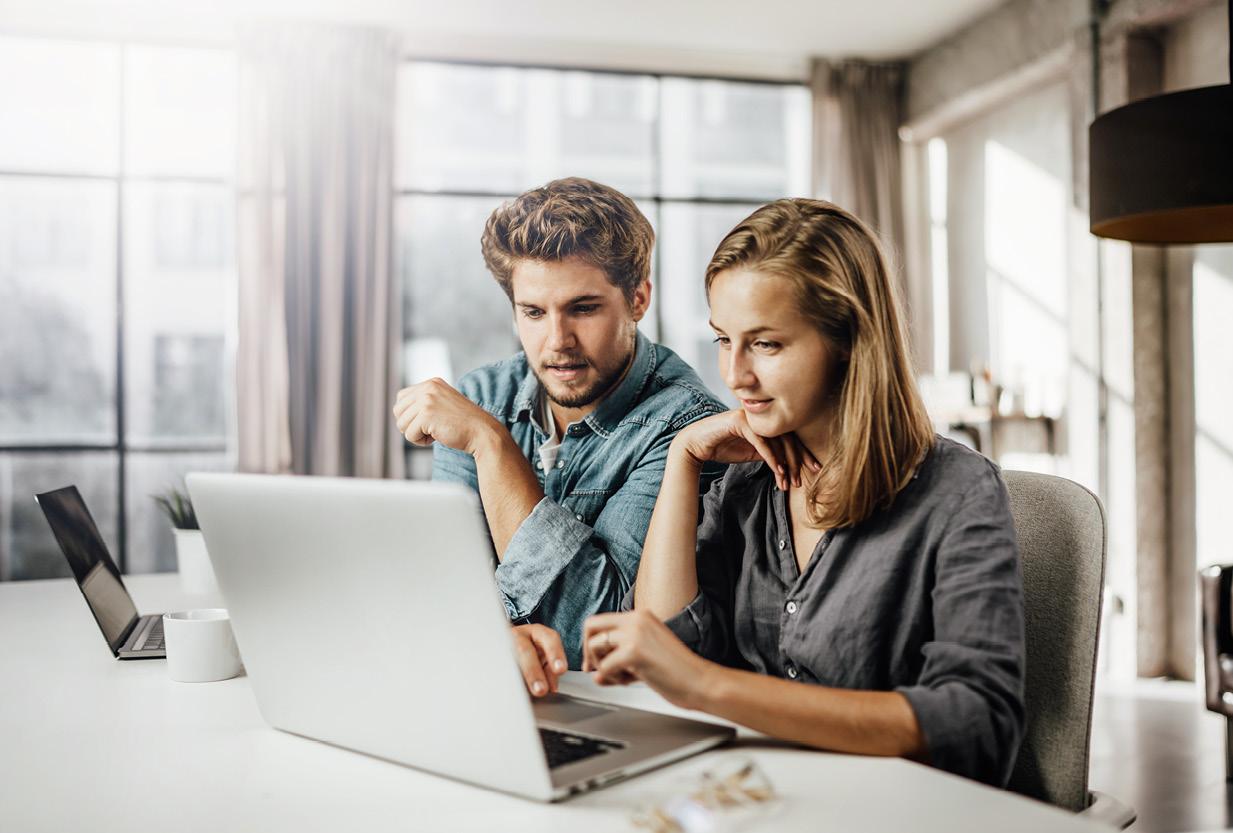Junge Frau und junger Mann sitzen mit zwei Laptops an einem Tisch