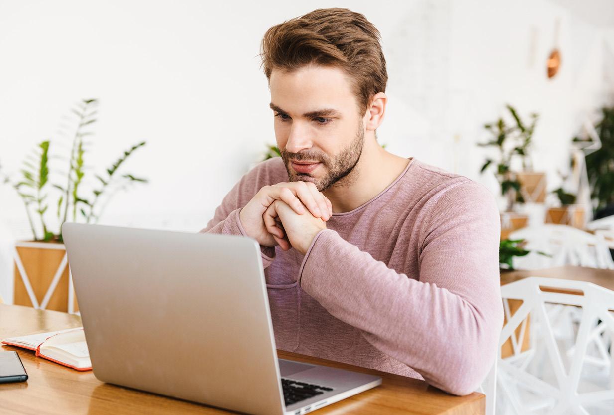 Mann sitzt am Tisch und schaut konzentriert in einen Laptop.