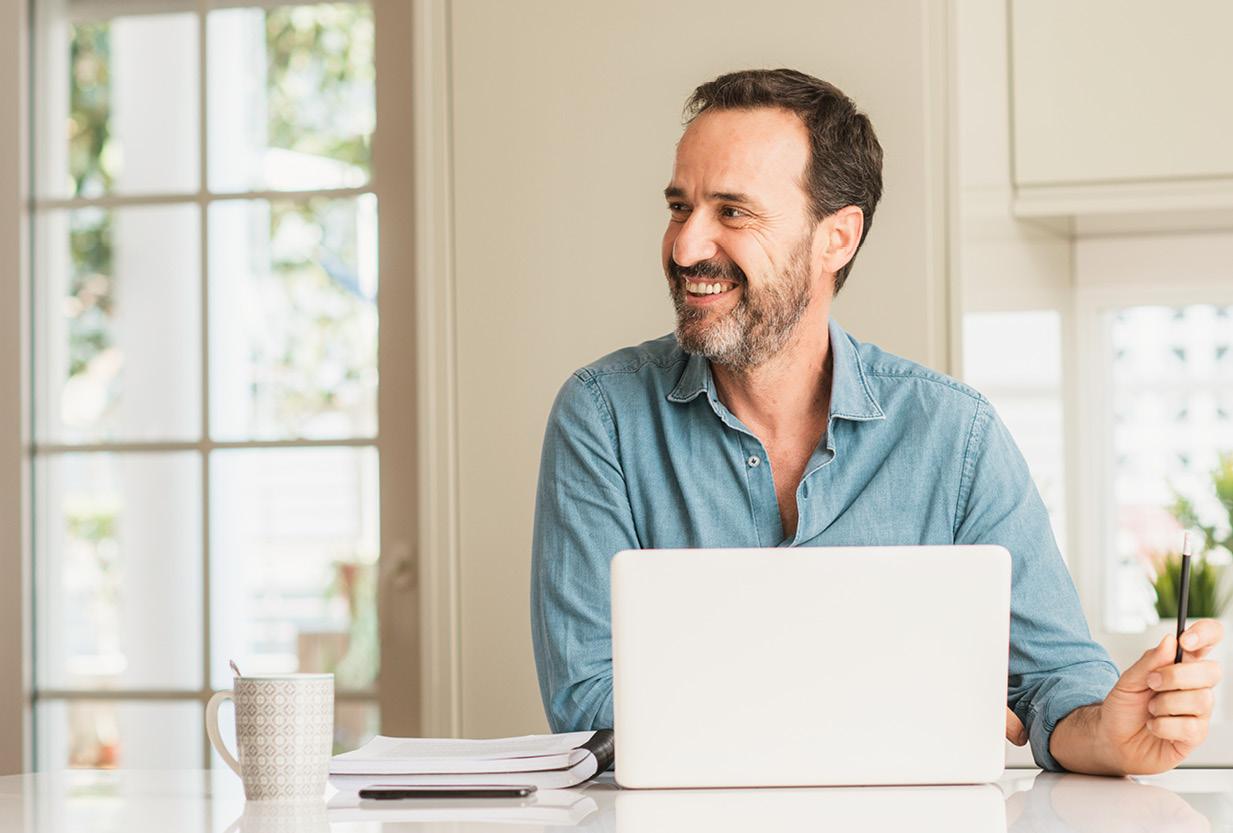 Mann mittleren Alters sitzt am Tisch am Laptop