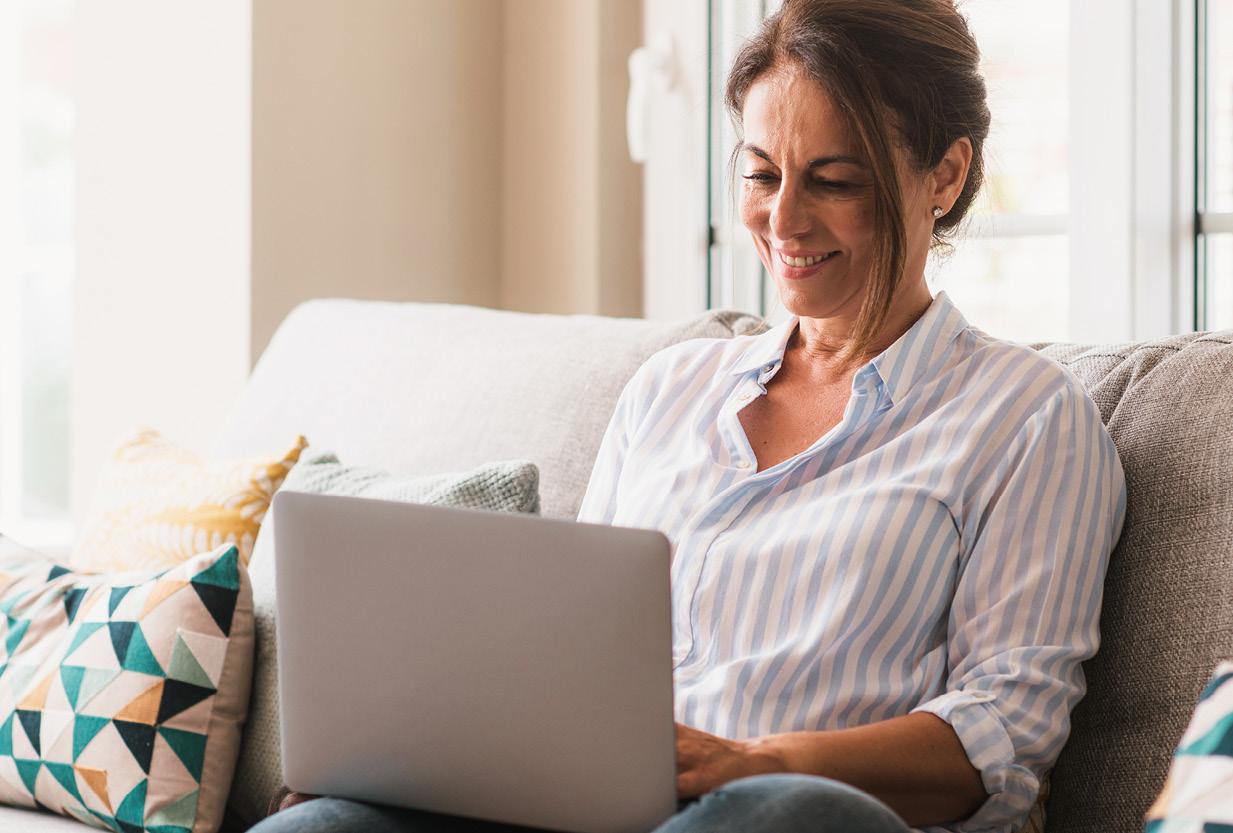 Frau mittleren Alters sitzt mit Laptop auf einer Couch und lächelt