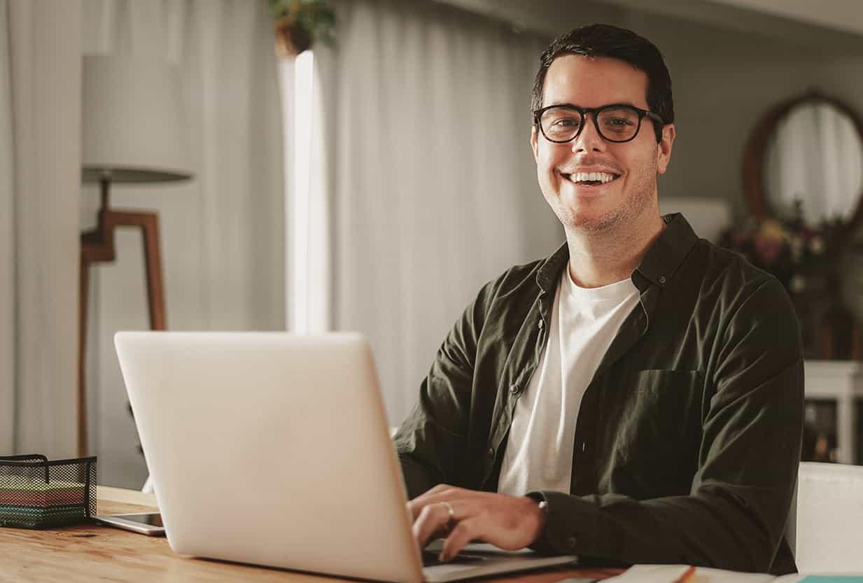 Mann mittleren Alters und Brille sitzt an einem Laptop und lacht in die Kamera