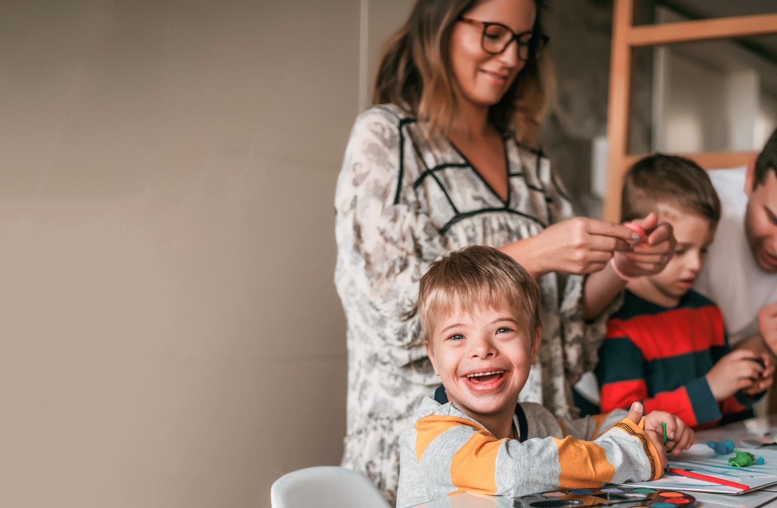 Kind sitzt lachend am Basteltisch, im Hintergund zwei erwachsene und ein weiteres Kind