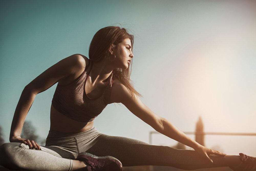 Frau sitzt und dehnt die Beinmuskulatur.