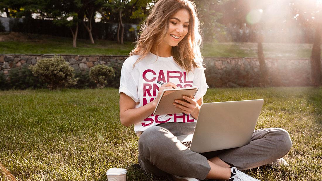 Junge Frau sitzt mit Laptop auf dem Schoß im Gras.