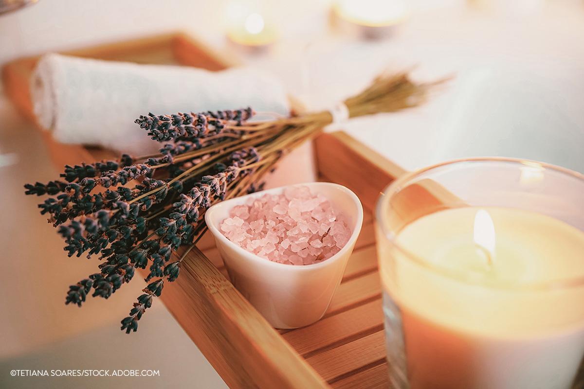 Eine Kerze, ein Lavendelbündel und ein Handtuch auf einem Brett über der Badewanne.