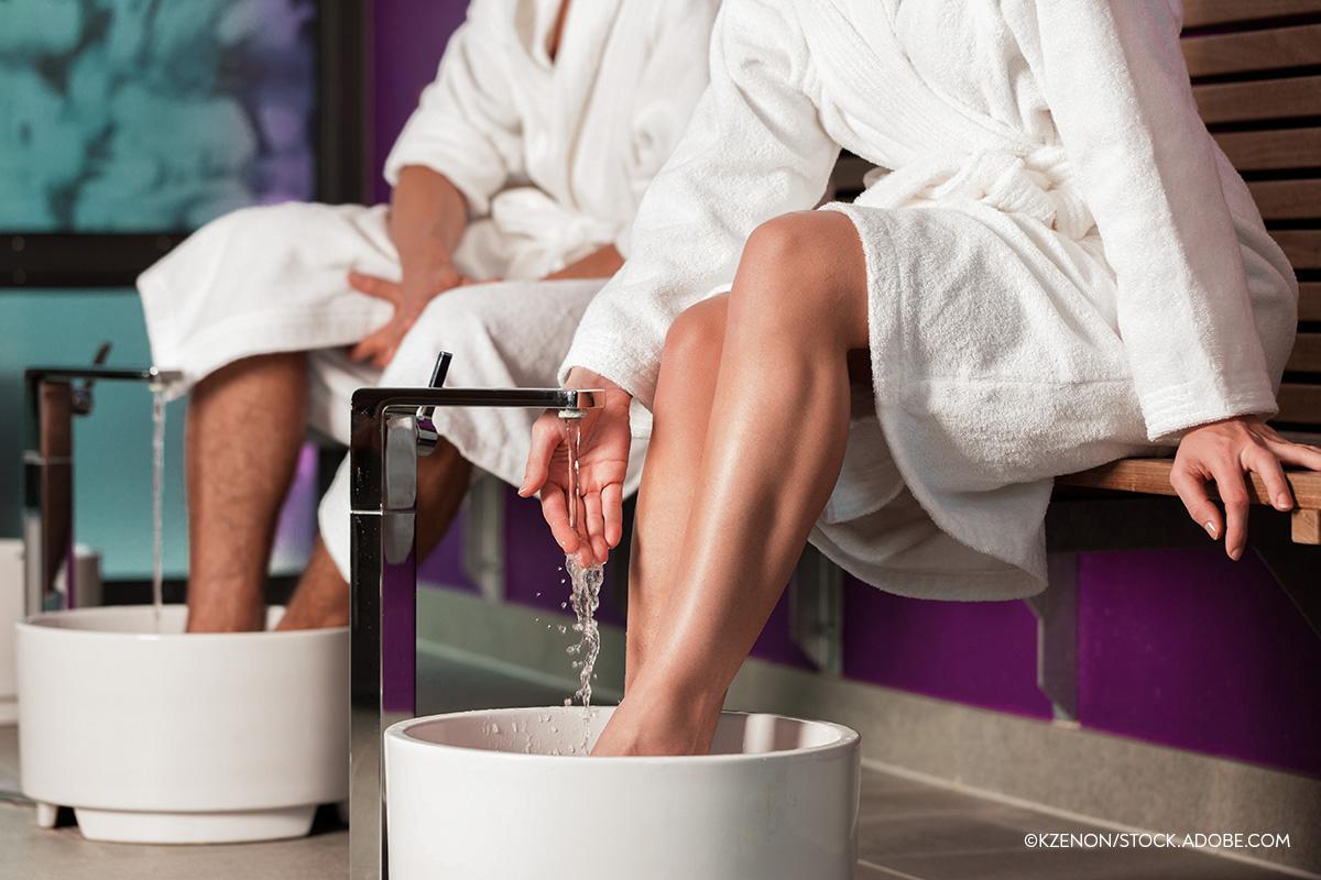 Zwei Menschen halten ihre Füße in ein Fußbad, die vordere Person überprüft die Wassertemperatur.