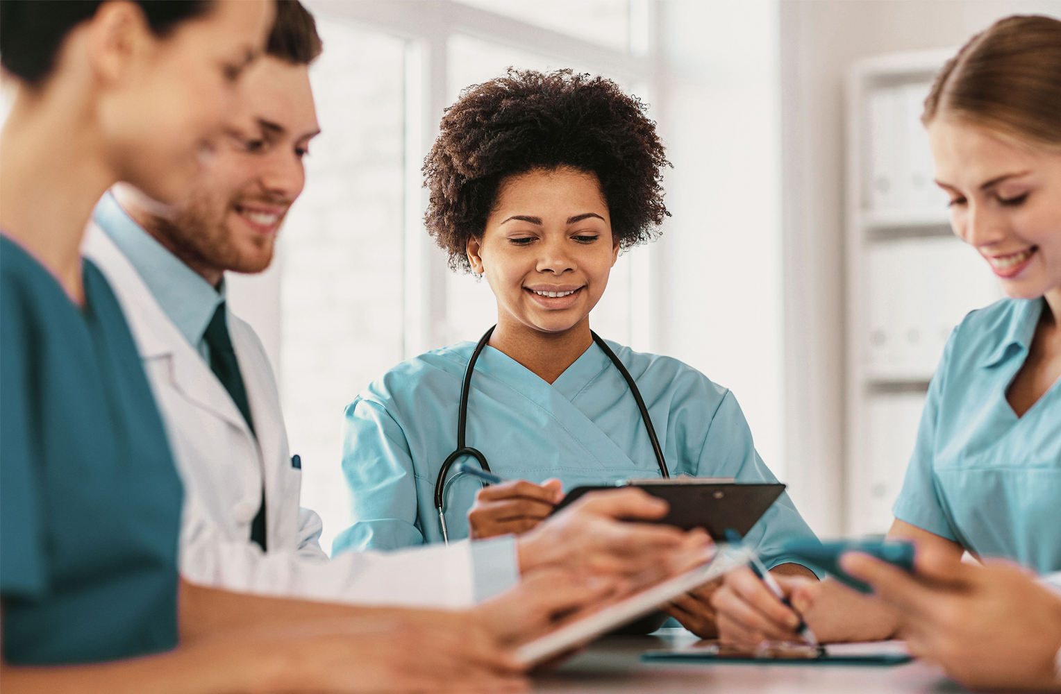 Vier junge Menschen in Arztkleidung sitzen um einen Tisch herum.