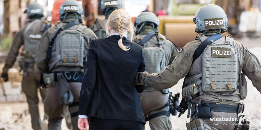 Polizisten eskortieren Frau