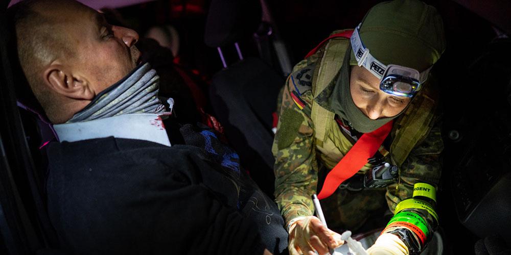 Soldatin mit Stirnlampe versorgt einen Mann