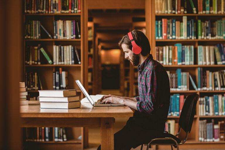 Mann mit roten Kopfhörern sitzt an einem Tisch in der Bibliothek vor einem Laptop
