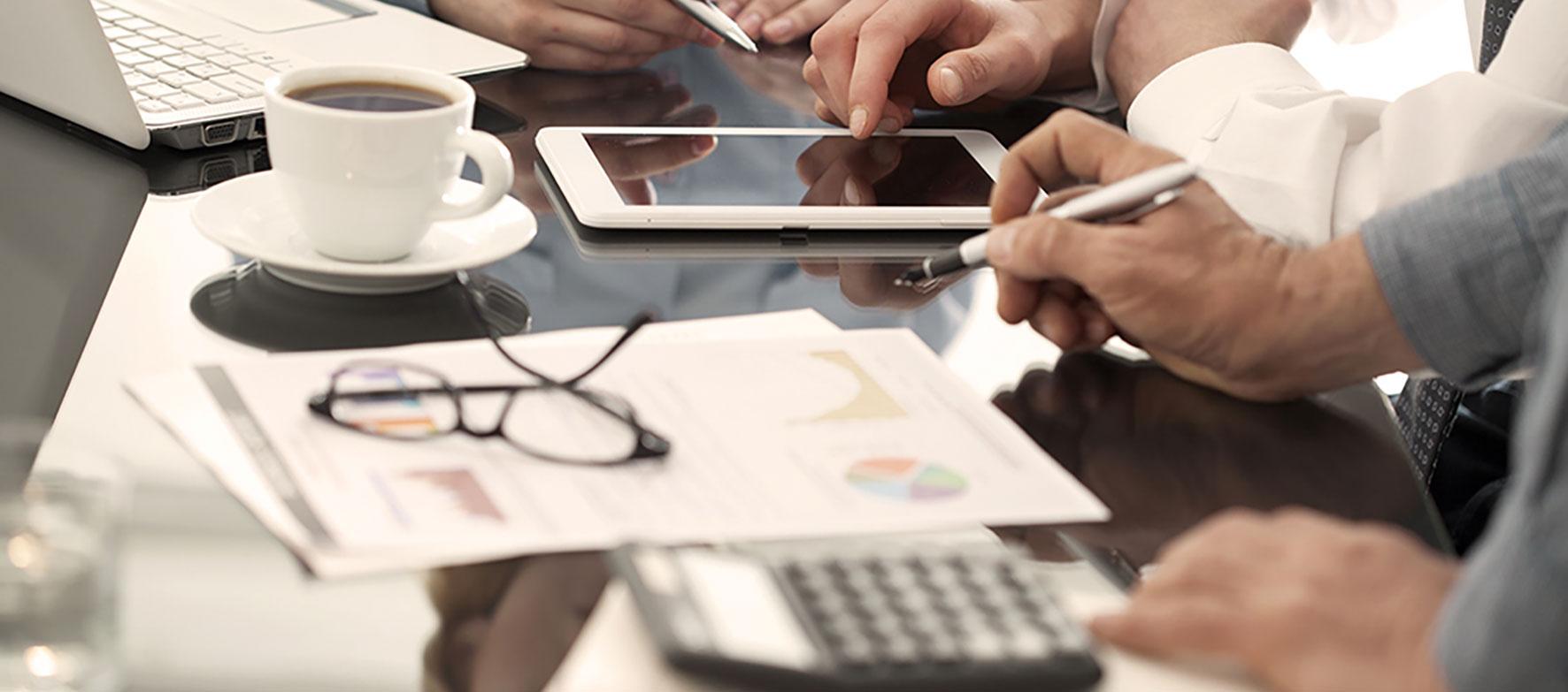 Mehrere Hände an einem Tisch über Kalkulationstabellen und Taschenrechner.