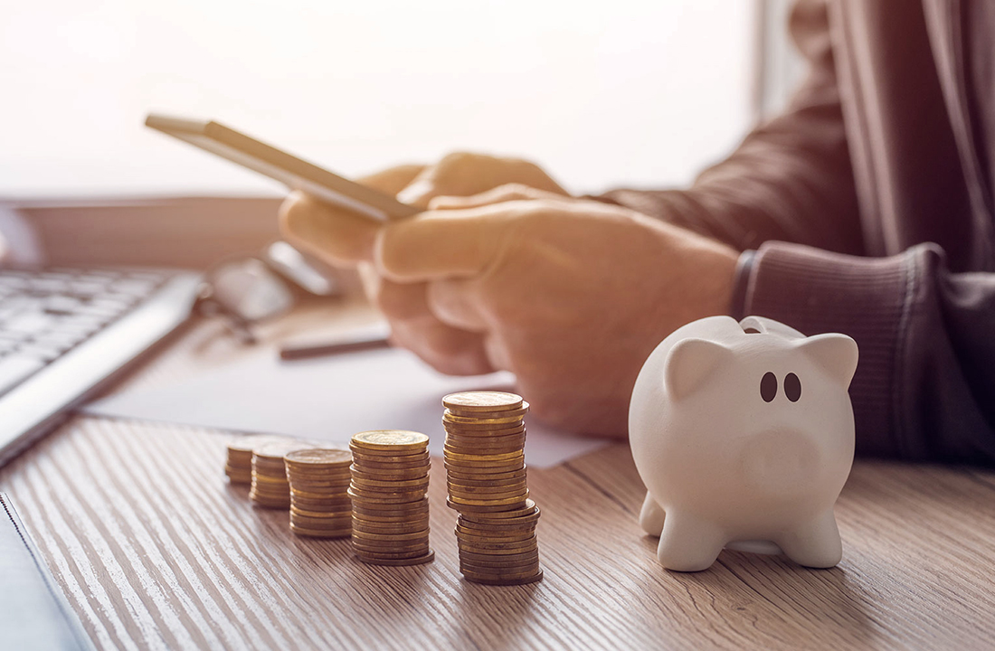 Kleines Sparschwein neben Türmchen aus Münzen, Hände mit Taschenrechner im Hintergrund.