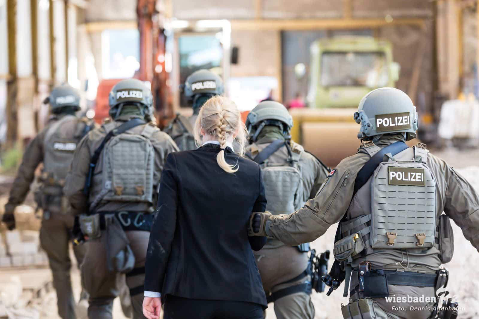 Eine Frau in schicker Kleidung wird von mehreren Polizisten in Einsatzkleidung weggeführt.