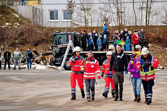 Feuerwehrleute und Zivilisten im Vordergrung, im Hintergrund ein Truck, auf dessen Ladefläche viele Leute stehen.