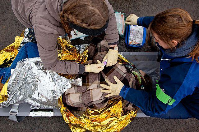 Zwei Frauen führen erste Hilfe bei einem Menschen durch, der auf einer Trage liegt und mit einer Wärmefolie bedeckt ist.
