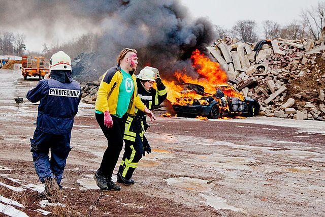 Ein Feuerwehrmann führt eine verletzte Person von der Unfallstelle fort. Im Hintergrund brennt etwas.