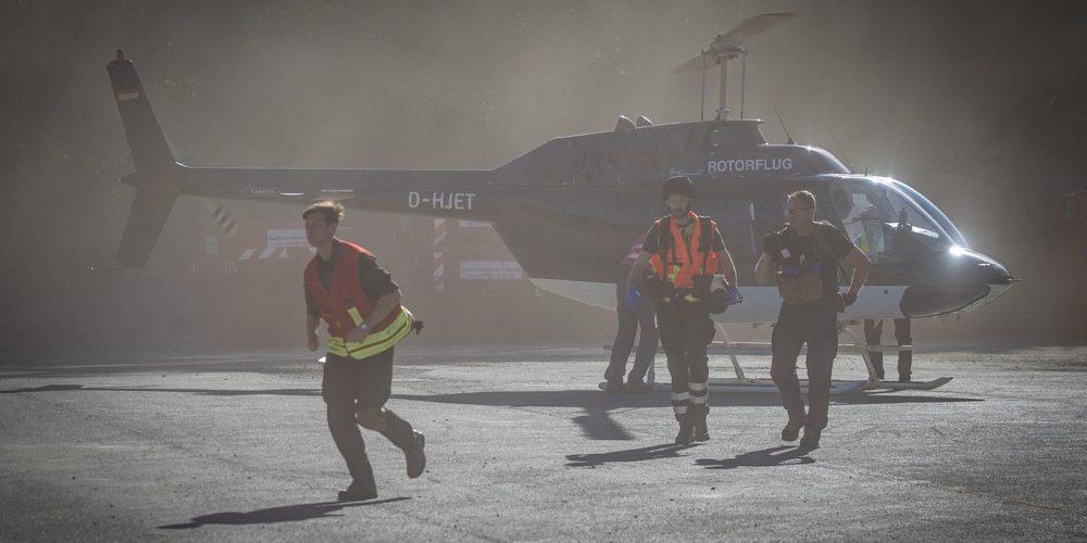 Mehrere Rettungshelfer gehen von einem Helikopter weg