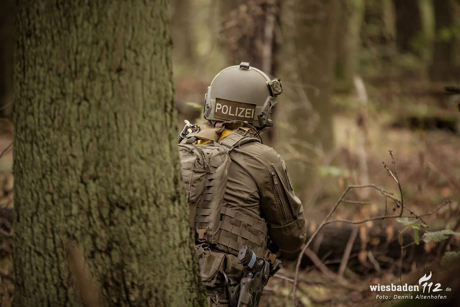 Mensch in Polizei-Einsatzkleidung steht im Wald, den Rücken zum Betrachter gedreht.