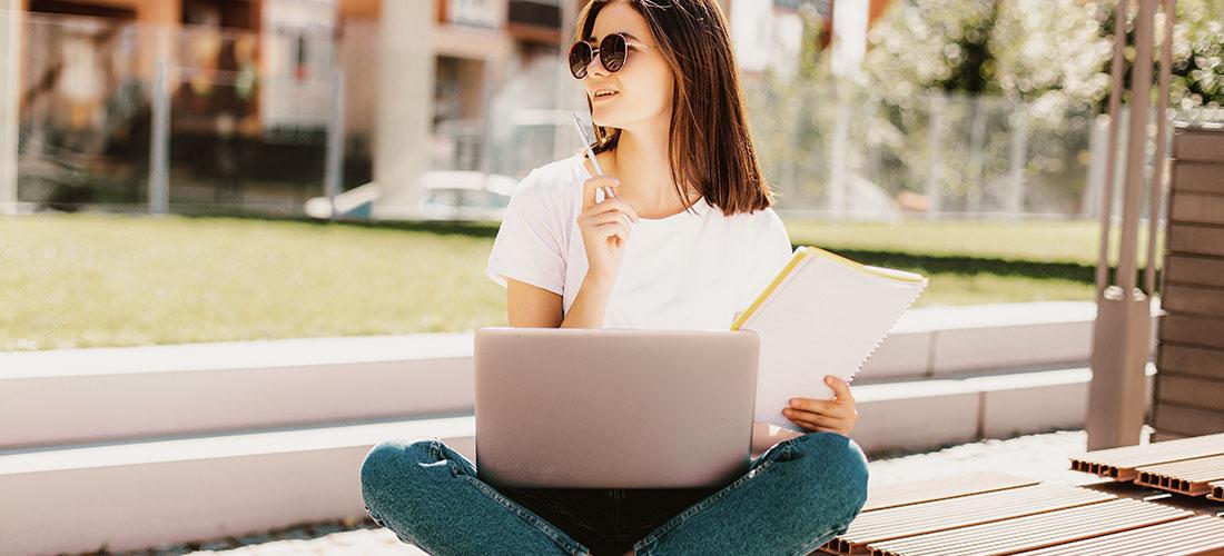 Junge Frau sitzt draußen mit Laptop und Collegeblock auf dem Schoß.